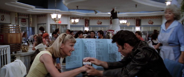 Lucky for him, it somehow works! Sandy immediately takes him back, and the first thing he does is try and hide her from his friends at the diner. Classy!