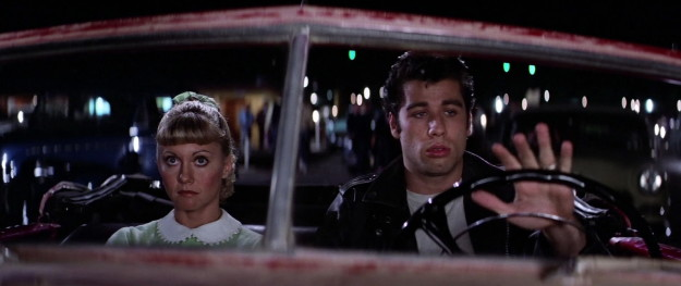 At some point OFF SCREEN, Danny and Sandy talk on the phone and he gives her a half-assed apology and lures her to a drive-in movie...