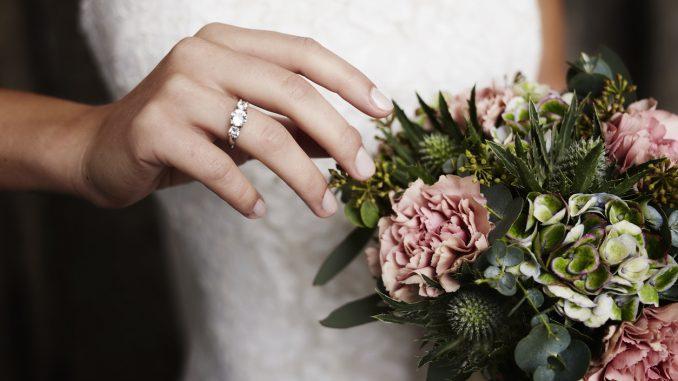 Bride wearing wedding ring near flowers