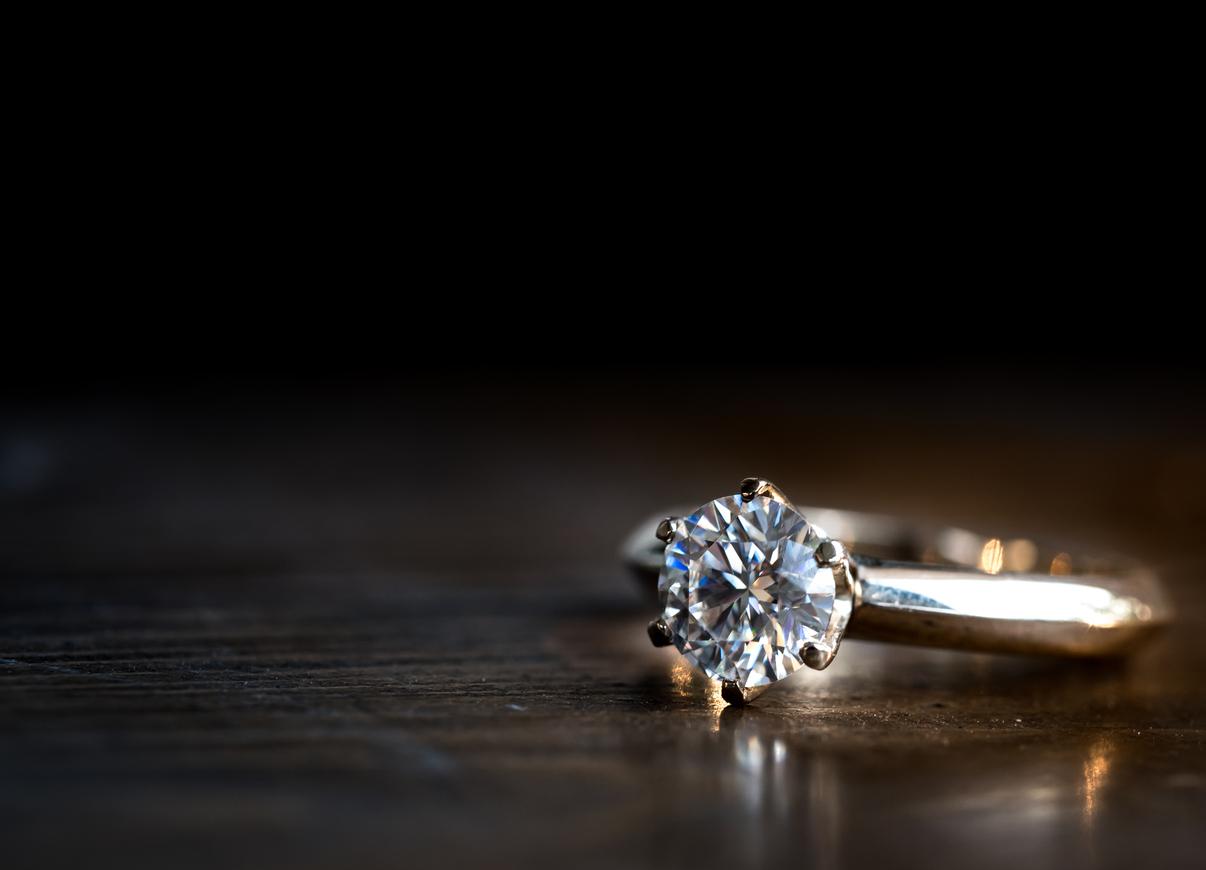 golden diamond ring on the wooden table